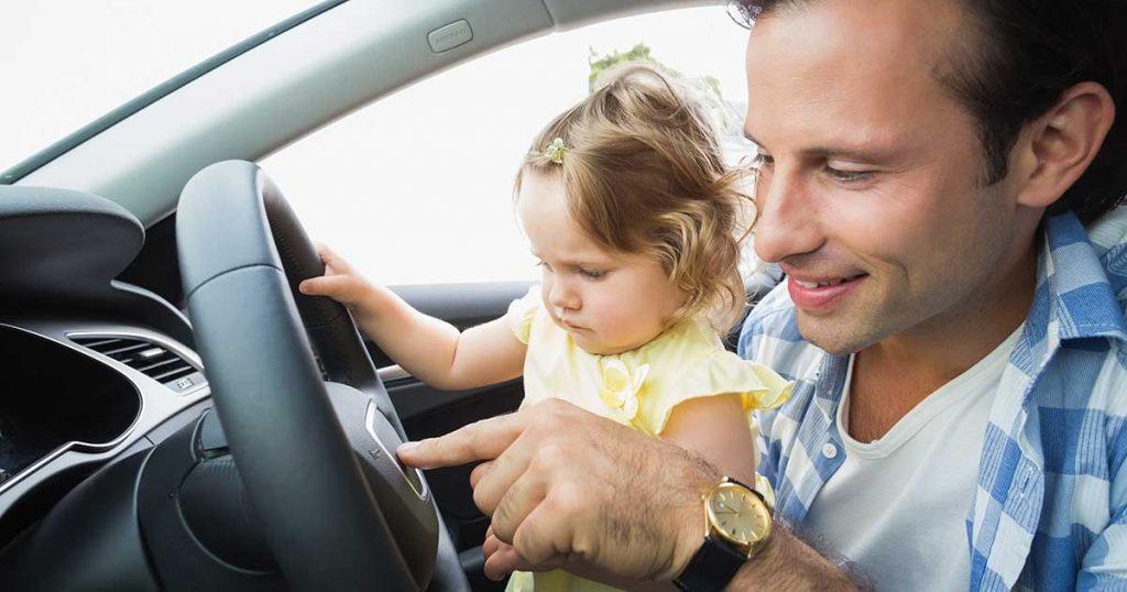 dad showing steering wheel to daughter
