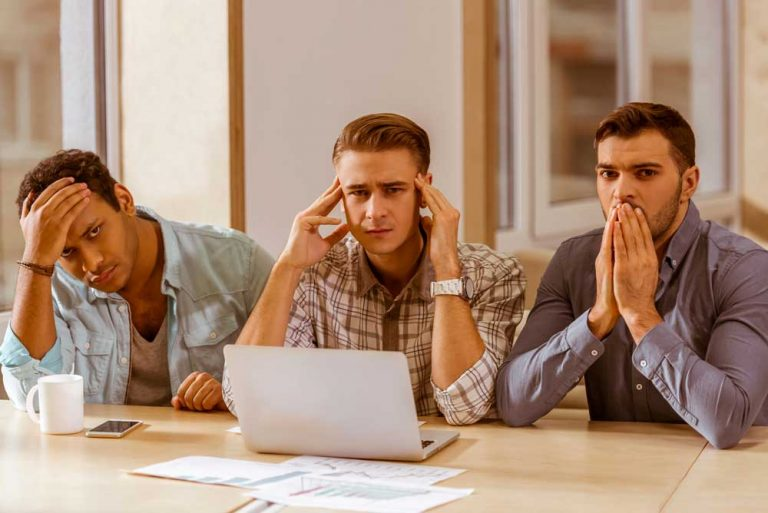 three young businessmen working looking worried about brand crisis