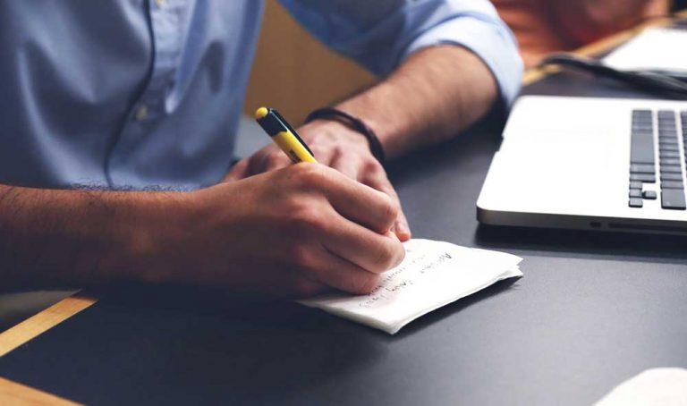 man taking notes on notepad
