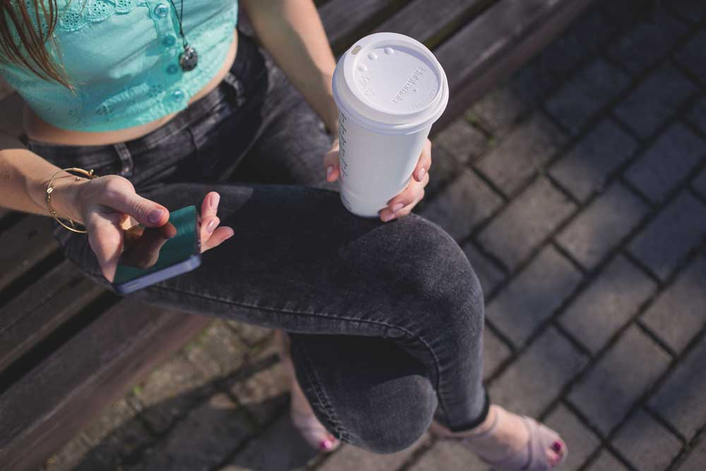 young woman with coffee in hand using self service on mobile phone