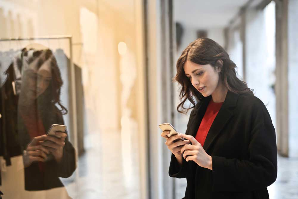 Woman Using Mobile to Browse While Shopping showing omnichannel retail customer experience