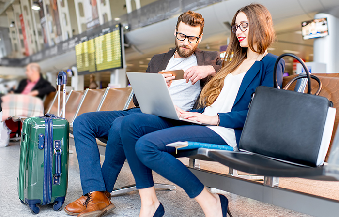 couple using devices at airport