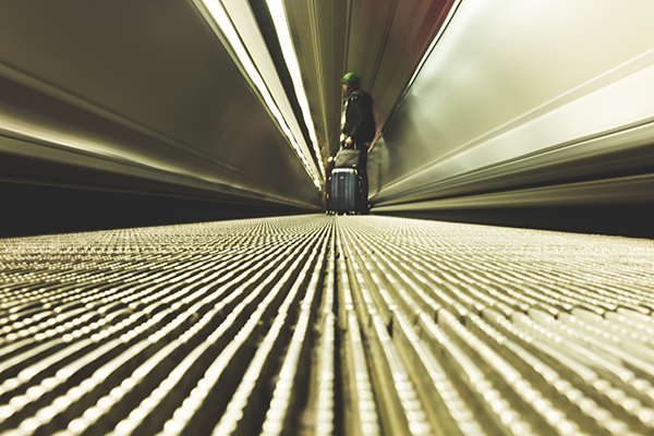 Rolling a suitcase down a moving walkway