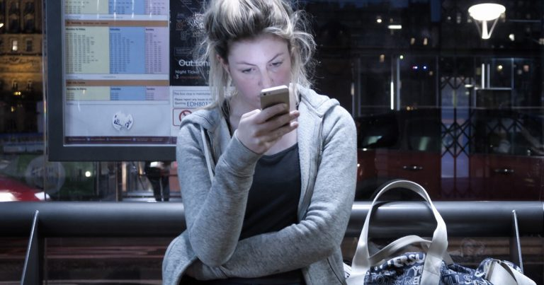 tired looking consumer staring at smartphone