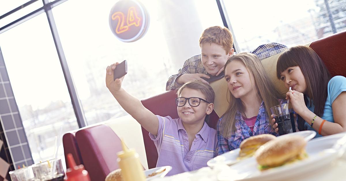 group of teens taking selfie at diner