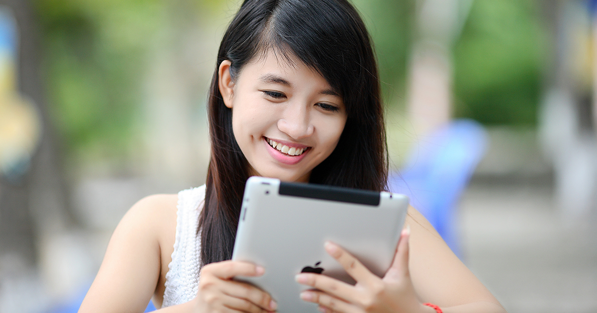 young woman smiling at ipad experiencing influencer marketing
