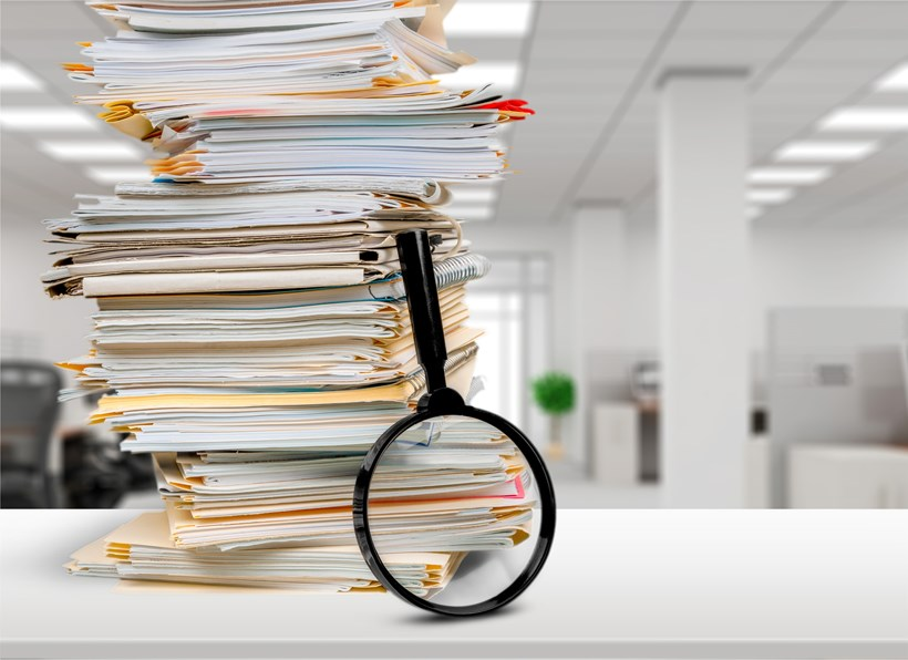 A stack of customer data sits on an agents desk, waiting for manual QA check.