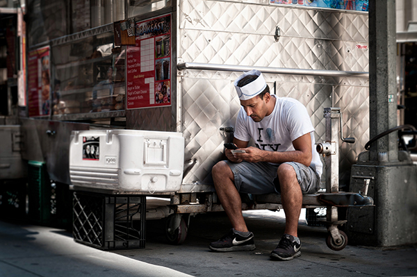 Foodtruck man using a smartphone to interact with Mobile Channels for Customer Service