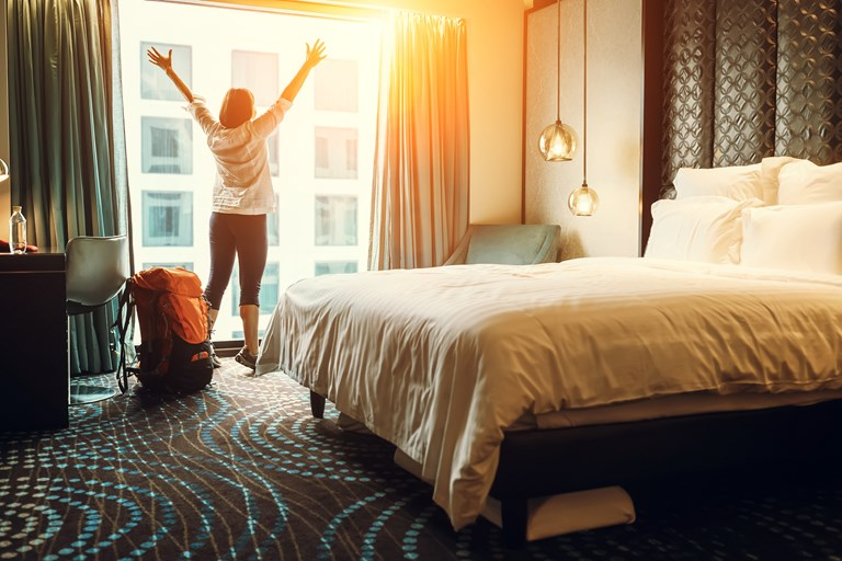 Millennial traveler looks out window happy after arriving in hotel room