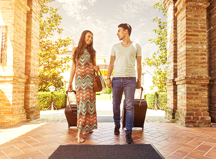 millennial couple enters hotel