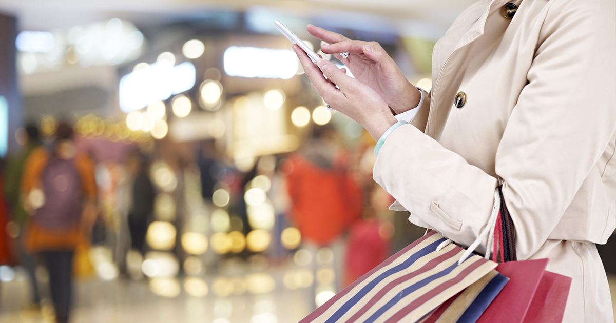 woman receiving proactive smartphone notification while shopping