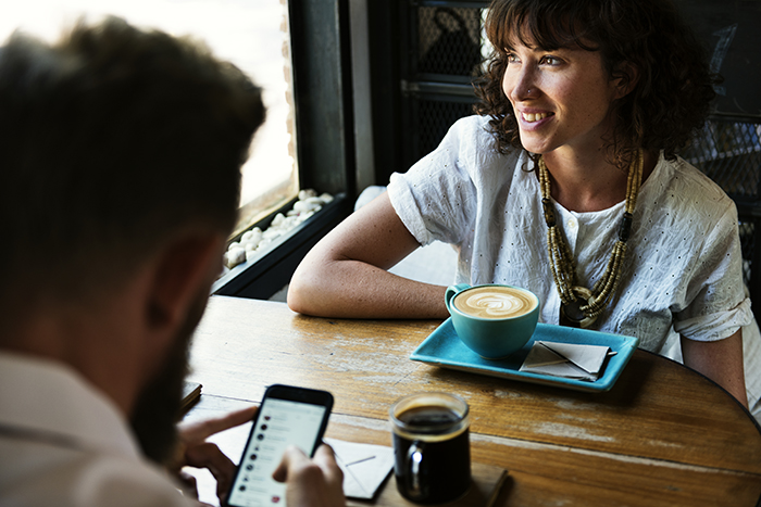 couple at coffee shop with smartphone