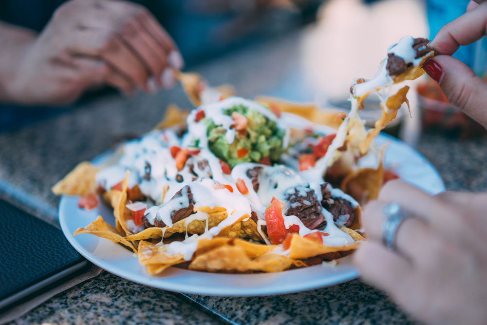 A group of millennial friends shares nachos on a night out at a new restaurant
