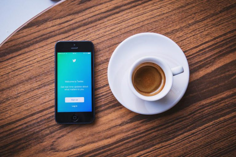 cup of coffee next to phone showing twitter login