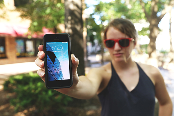 woman wearing sunglasses holding phone facing out