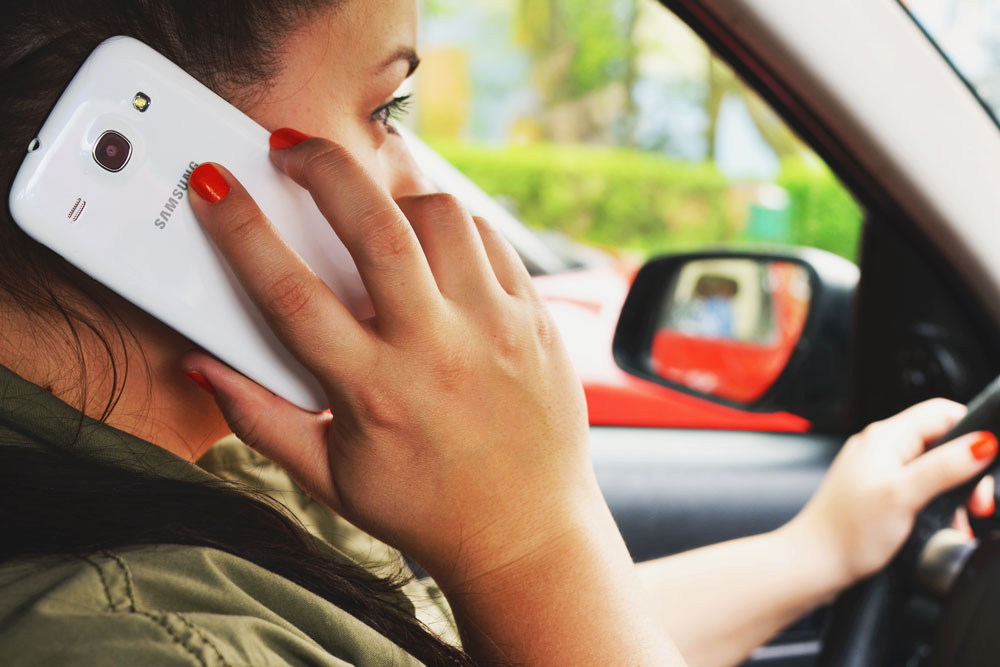 woman talking on smartphone while driving
