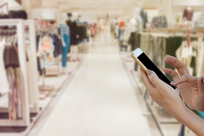 woman using iphone in store aisle
