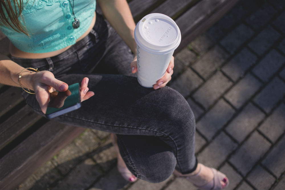 young woman with phone and coffee having digital customer experience