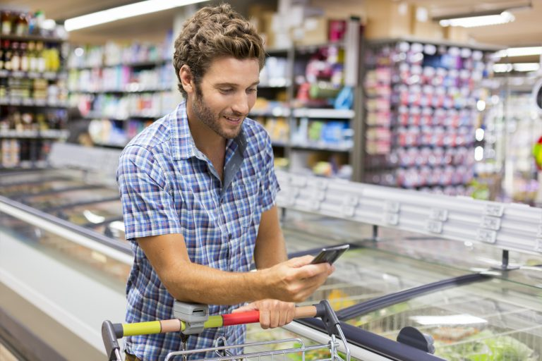 shopper looking at phone in grocery store