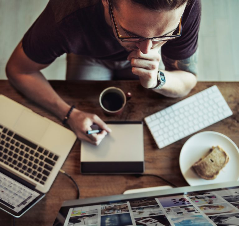 man working at desk to manage social ads