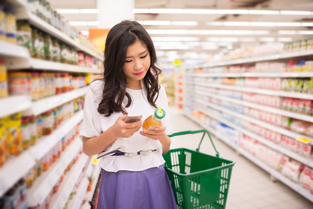 shopper in supermarket reading information on smartphone engaging with cpg experience