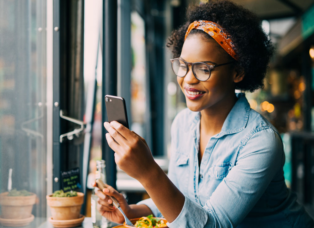 woman looking at phone while eating meal