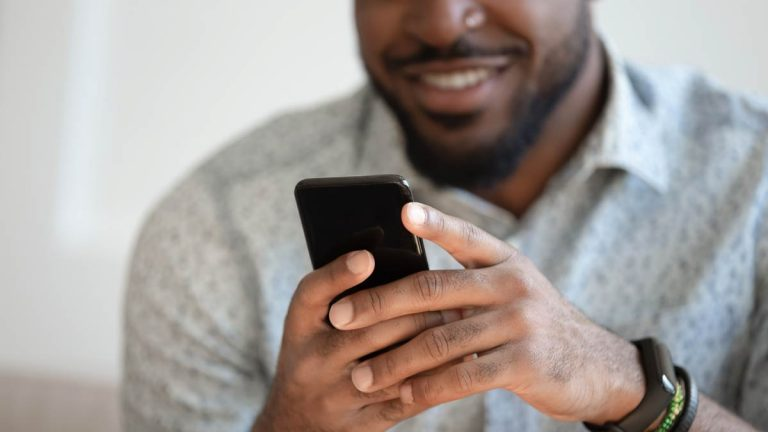 Man smiling using their mobile phone
