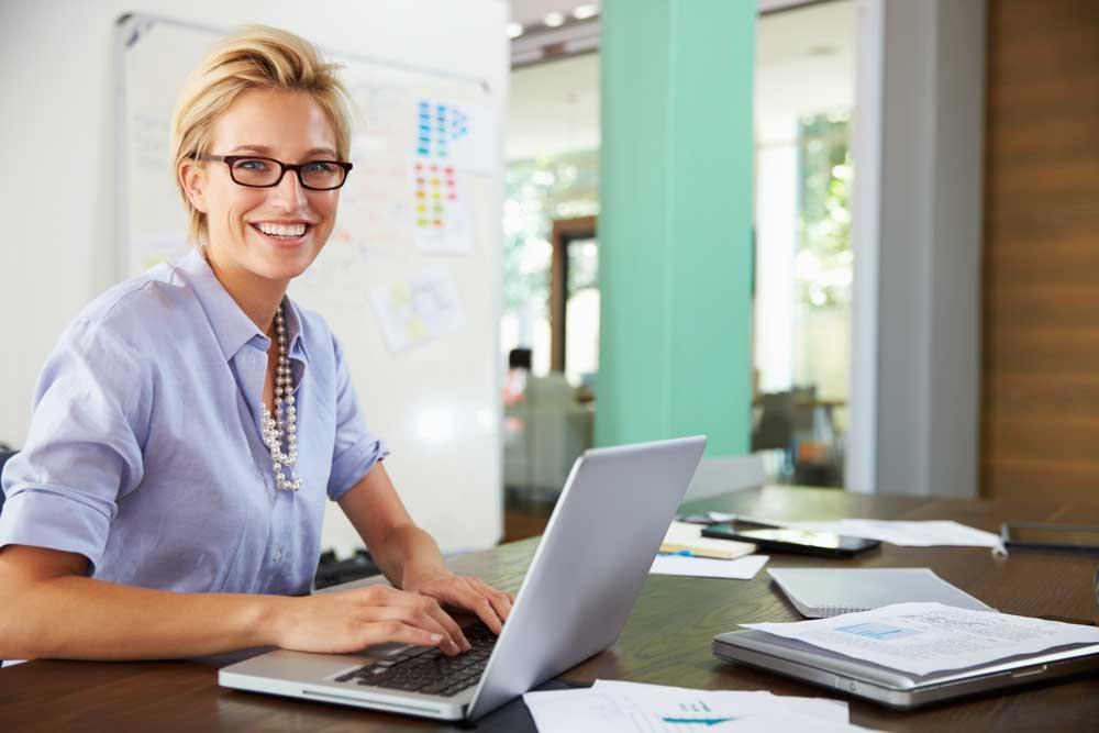 woman using hr help desk software on laptop
