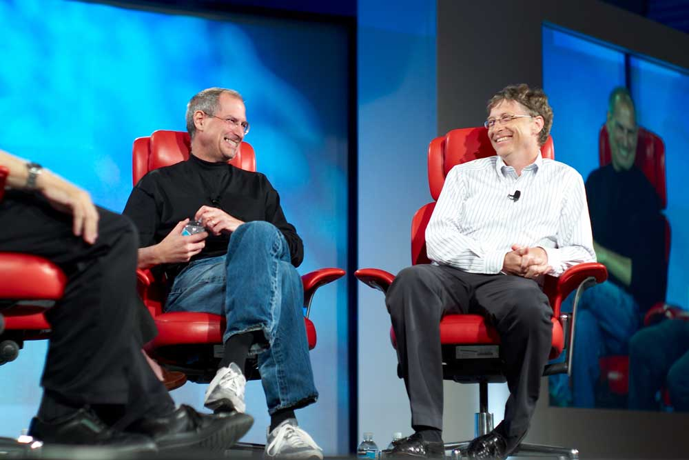 Steve Jobs and Bill Gates discussing at a conference
