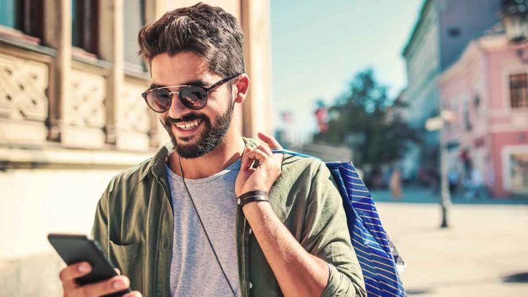 Person with sunglasses using mobile phone while shopping