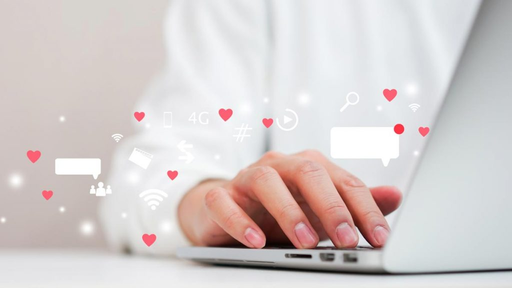 Person typing on laptop with social media reactions and comments appearing.