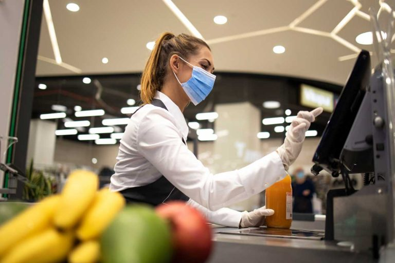 cashier wearing mask at grocery store check out